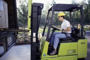 Side profile of a young man driving a forklift